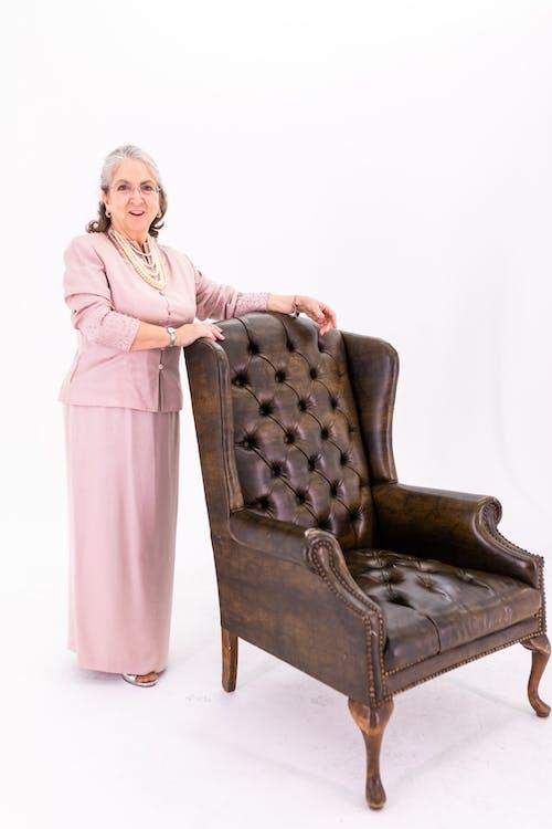 Woman in Pink Long Sleeve Dress Standing Beside Brown Wooden Armchair