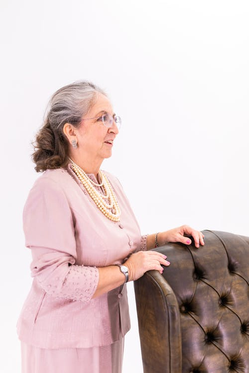 Elderly Woman Standing Near A Leather Chair
