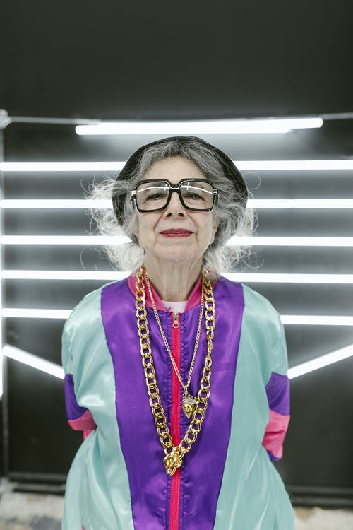 Elderly Woman Wearing Colorful Outfit With Flashy Jewelry