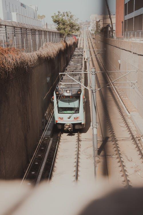 White and Green Train on Rail Tracks