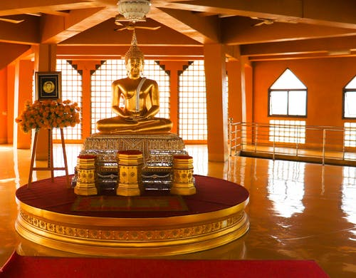 Interior of modern Asian temple with big golden Buddha statue in center in daylight