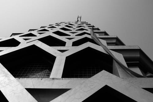 Black and white low angle exterior of contemporary high rise building with geometric symmetrical shapes under gray sky