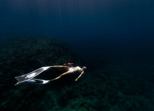 Woman snorkeling in dark blue sea