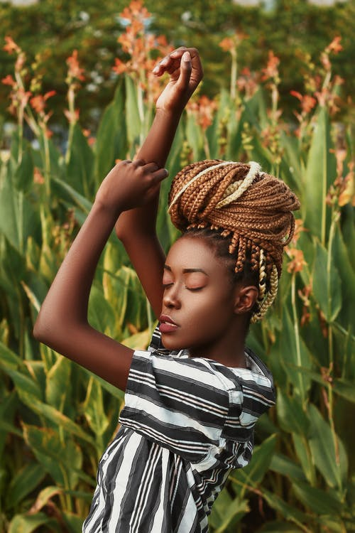Side view of young African American female with braids in casual clothes standing with raised arms and closed eyes among green trees in countryside in sunny day