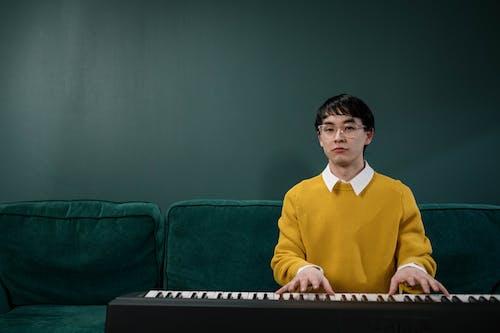 Man in Yellow Sweater Playing Piano