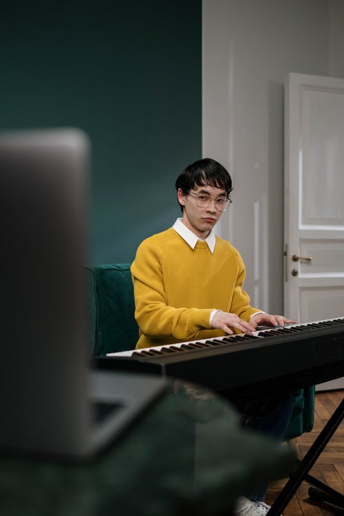 A Man Sitting on the Sofa Playing Piano