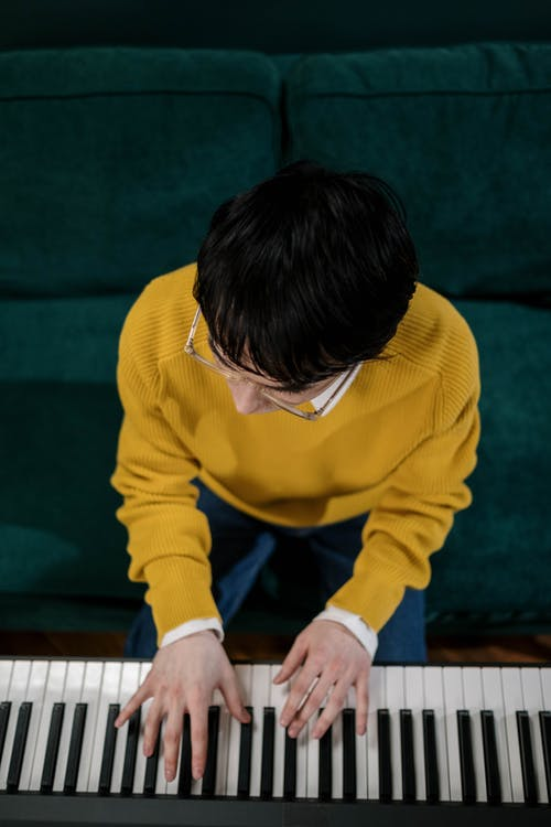 A Man in Yellow Sweater Playing Piano