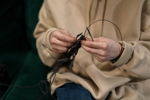 Close-Up Photo of a Person's Hands Knitting