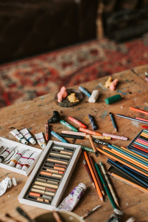 Pencils, Oil Paint and Pastel Crayons on Wooden Table