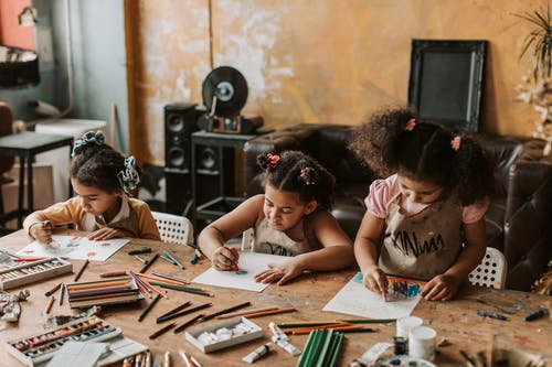 Three Girls Drawing at the Table