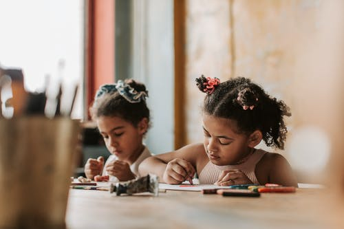 Little Girls Drawing at the Table