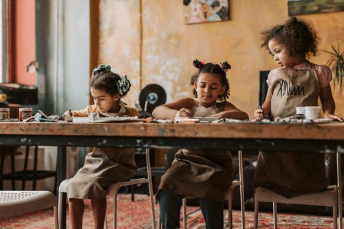 Girls Sitting near Brown Wooden Table