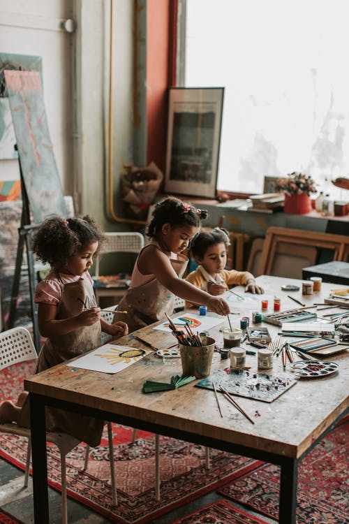 Girls Painting on Brown Wooden Table
