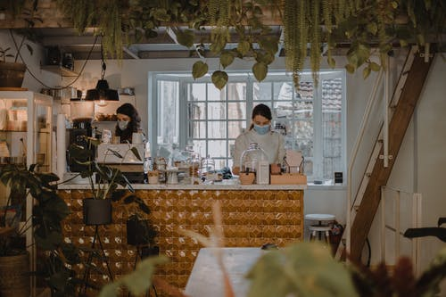 Women in medical masks working behind counter in cafe with plants