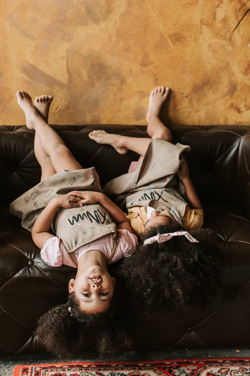 Girls in Brown Apron Lying Upside Down on Leather Sofa