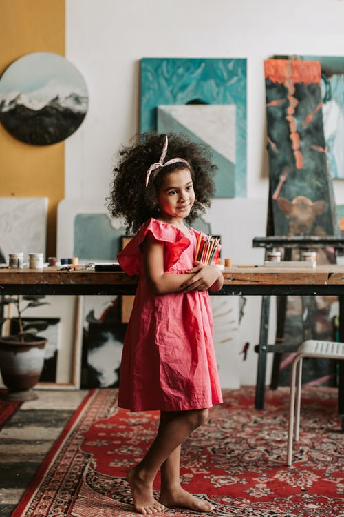 Girl in Pink Dress Standing near Brown Wooden Table