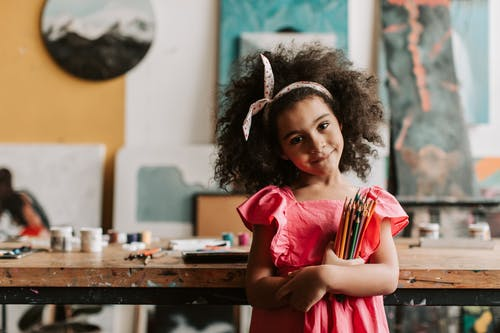 Girl in Pink Dress Holding Colored Pencils