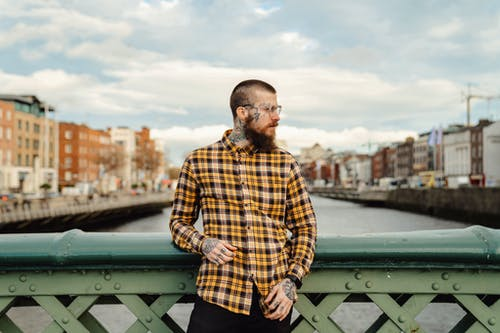 Man in Brown and White Plaid Dress Shirt Standing on Bridge