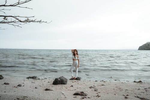 Woman in White Tank Top and White Pants Standing on Gray Rock Near Body of Water