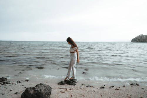 Woman in White Dress Standing on Gray Rock Near Body of Water