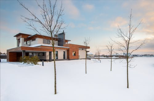 Exterior design of new residential two storey house with modern stone and wooden facade and spacious yard located in suburban area in wintertime