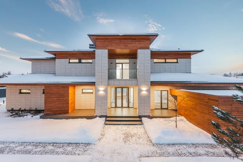Backyard view of new modern luxurious cottage house with stone and wooden facade and illumination in winter countryside