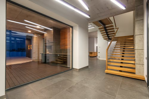 Interior design of contemporary spacious suburban house hallway with large panoramic window and wooden steps leading to second floor