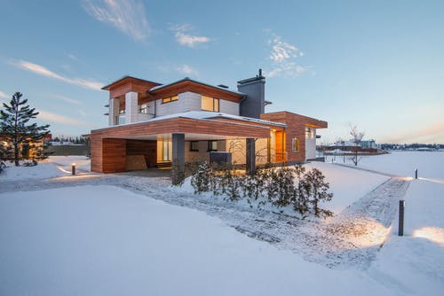 Exterior view of luxurious residential house with roofed parking and spacious backyard in snowy winter countryside