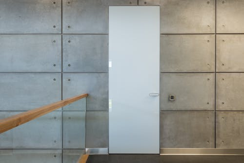 White interior door and gray stony tiled walls in hallway of contemporary loft style house