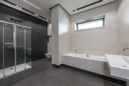 Interior design of contemporary spacious bathroom with shower cabin and bathtub in white and gray tones in modern house