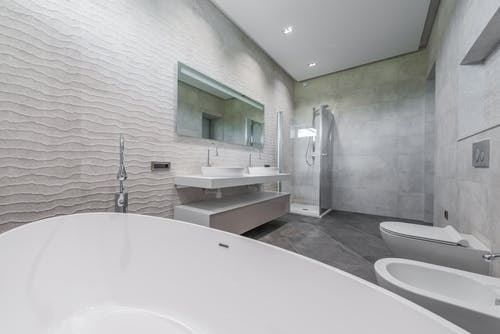 Contemporary minimalist luxury interior design of light bathroom with gray walls and floor furnished with double washbasin and bathtub in modern house
