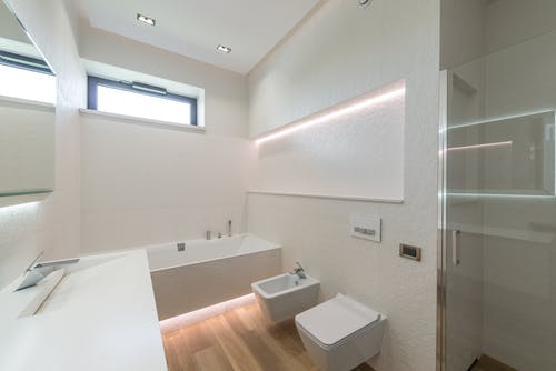 Interior design of modern minimalist luxury style bathroom with white walls and LED illumination equipped with washbasin and toilet and sink and bathtub