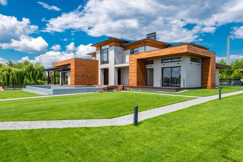 Exterior of contemporary residential house with green yard and paths near forest in summer