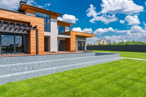 Exterior of contemporary residential house with panoramic windows glass doors and green lawn in yard on sunny day against blue sky with white clouds