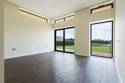 Interior of spacious room with wooden laminate floor big windows and glass door viewing terrace and green lawn
