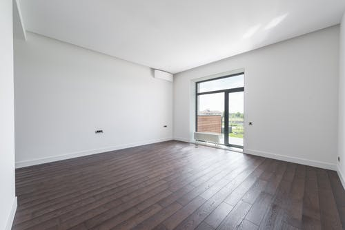 Empty room with balcony and parquet floor