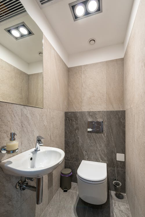 Interior of modern bathroom with ceramic sink and toilet bowl