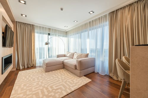 Comfortable sofa with cushions placed near windows covered with curtains in living room with kitchen set and soft carpet