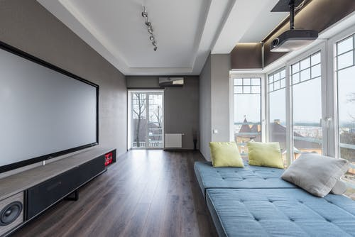 Comfortable settee with colorful cushions placed near big windows against contemporary television set in spacious room of modern stylish apartment