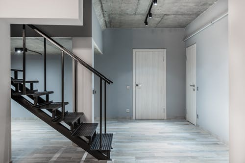 Black stairway with railing located in corridor of modern light spacious apartment with doors and laminate floor and glowing lamps