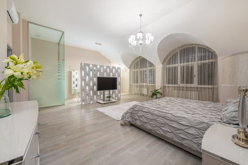 Comfortable bed with blanket placed near windows against modern TV in spacious bedroom with glass cabin and cupboard with flowers