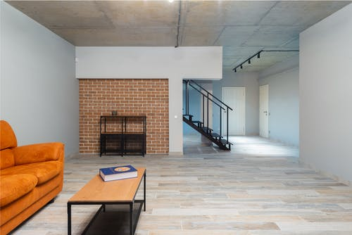 Orange comfortable sofa near table with book placed in stylish light spacious apartment with stairway brick wall and closed doors