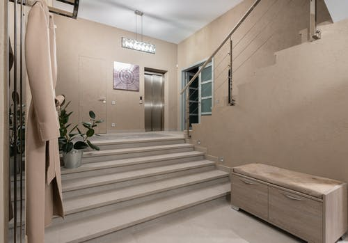 Spacious hallway of contemporary apartment with beige walls and wide stairway under glowing lamps
