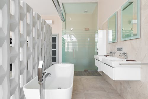 Modern bathroom with white bathtub and glass shower cabin and mirrors over basins
