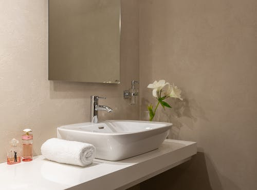 Interior of bathroom with white wrapped towel near ceramic basin and faucet with mirror on wall