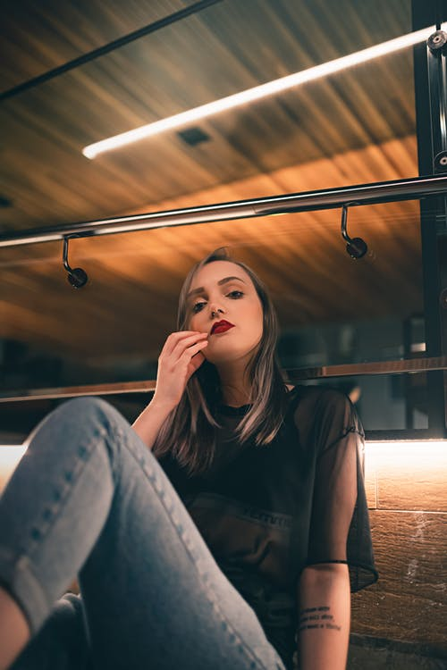 Young woman with red lips touching face