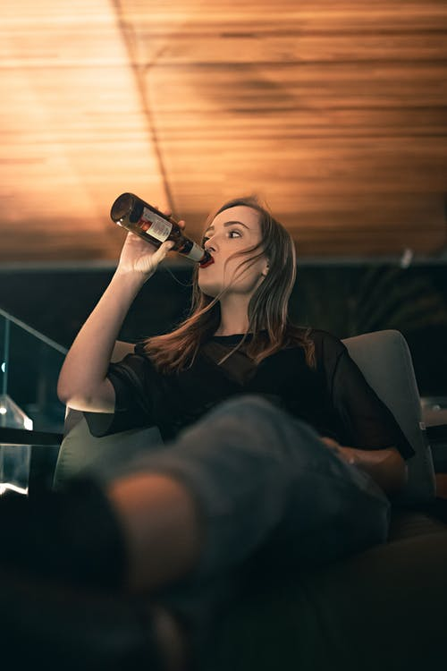 Young female drinking bottle of beer and relaxing in armchair in comfortable lounge in evening
