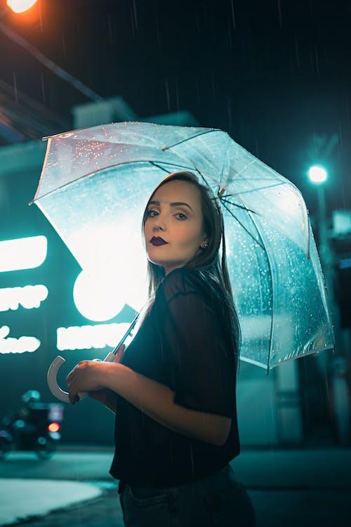 Pleasant content woman with umbrella in rainy evening