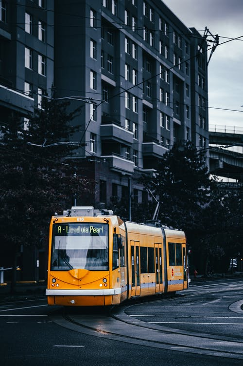 Yellow and White Tram on Road