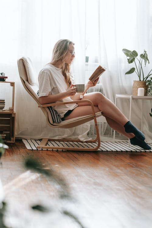 Young woman reading book in armchair near window